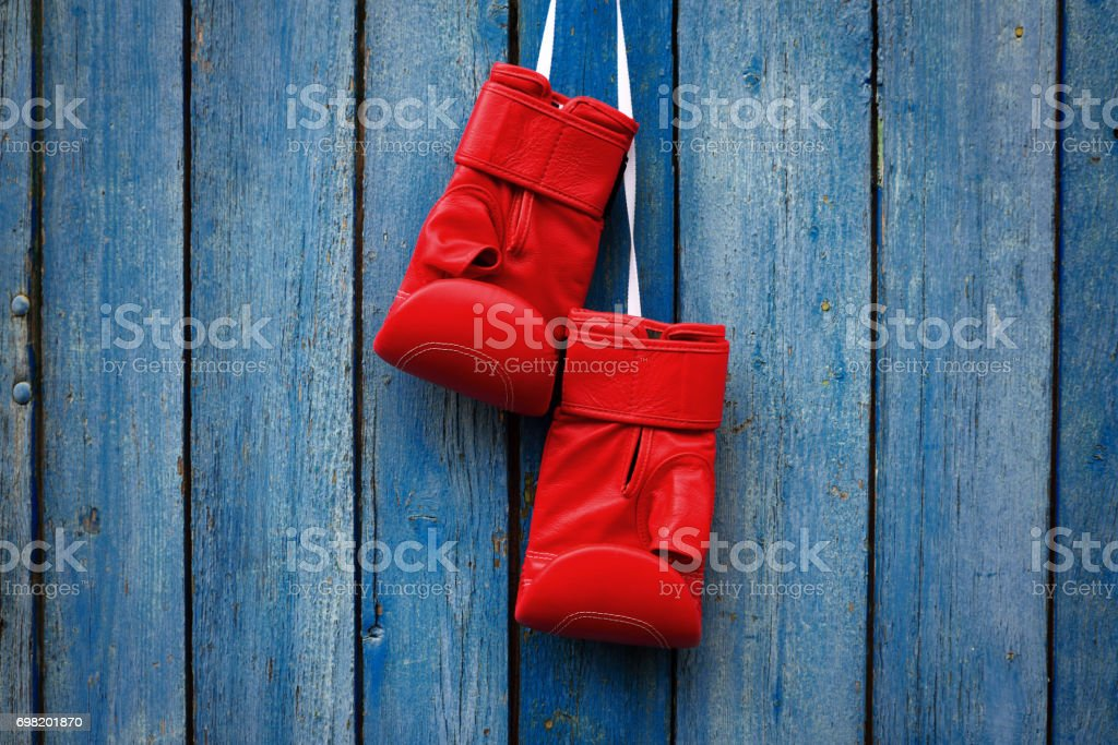 pair of red gloves for kickboxing hanging on a white rope stock photo