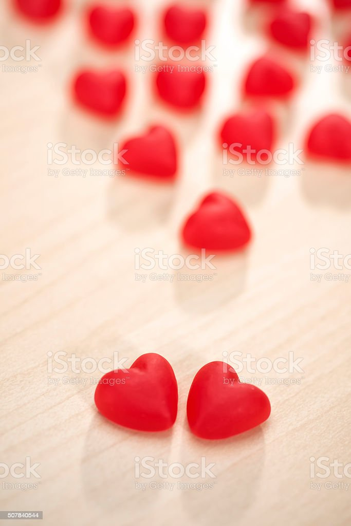 Pair of red heart shaped candies together in love stock photo