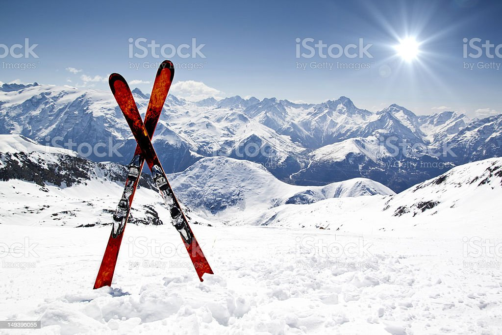 Pair of red skis crossed and wedged in snow on mountain stock photo