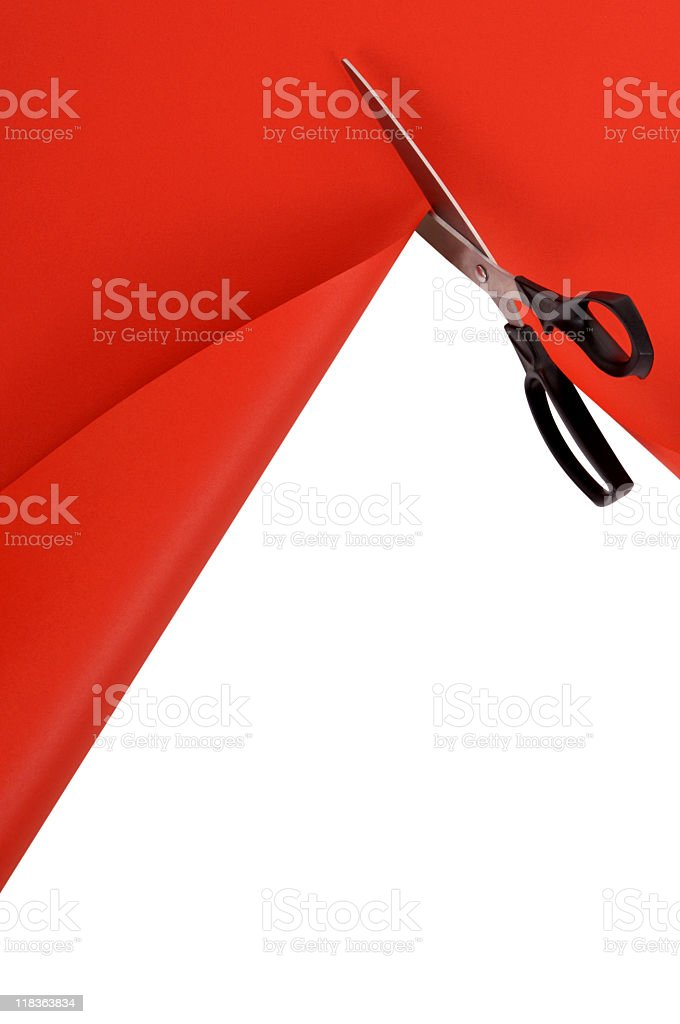 A pair of scissors cutting red paper stock photo