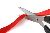 Pair of scissors cutting red ribbon