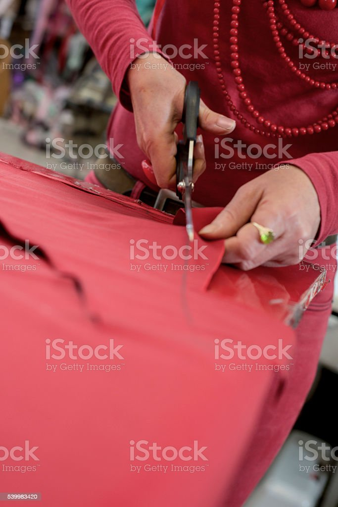 Pair of Scissors Cutting Through Red Cloth stock photo