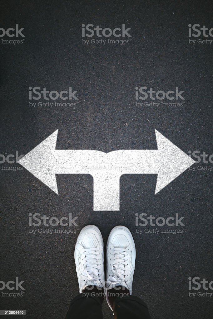 Pair of shoes standing on a asphalt with arrow sign stock photo