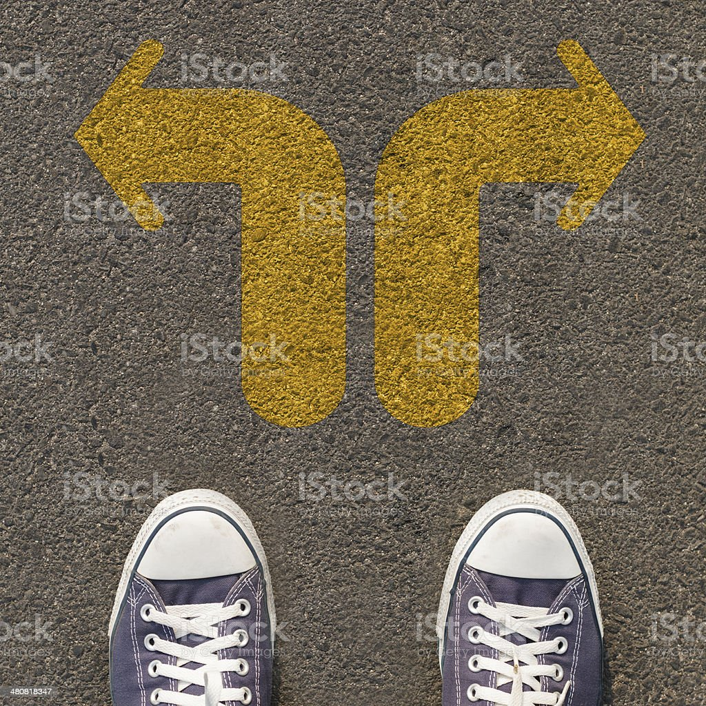 Pair of shoes standing on a road with arrow stock photo