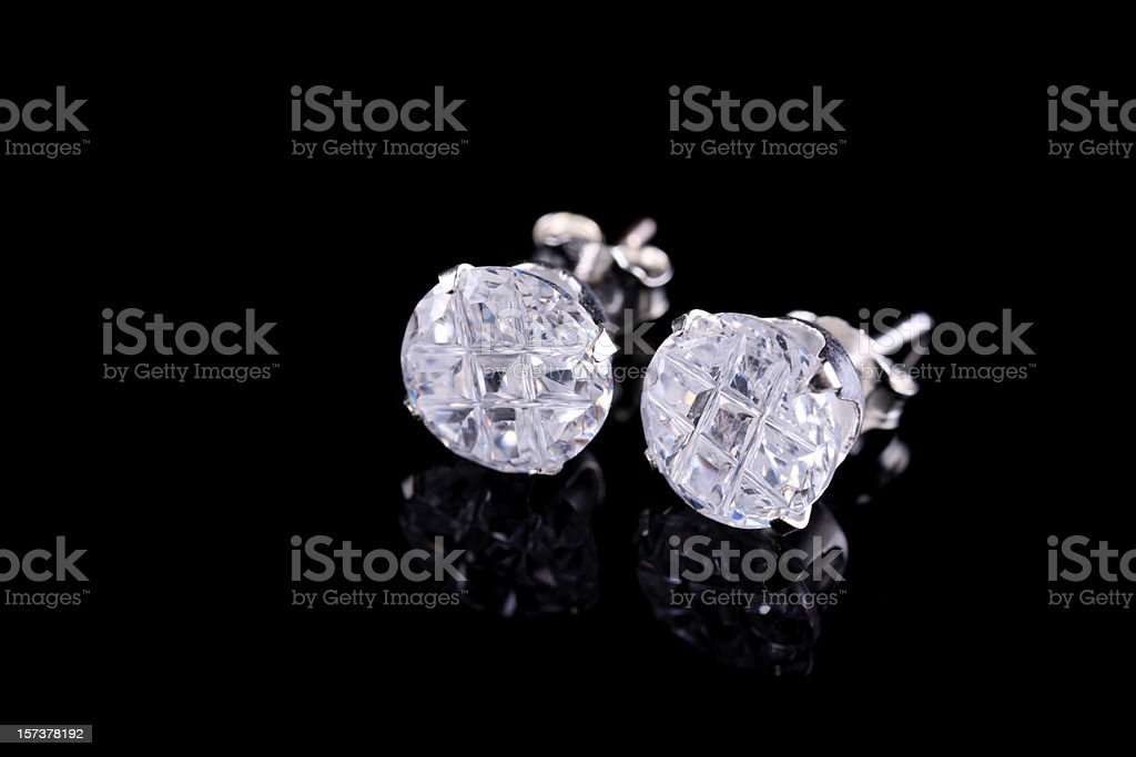Pair of silver diamond stud earrings on a black background stock photo
