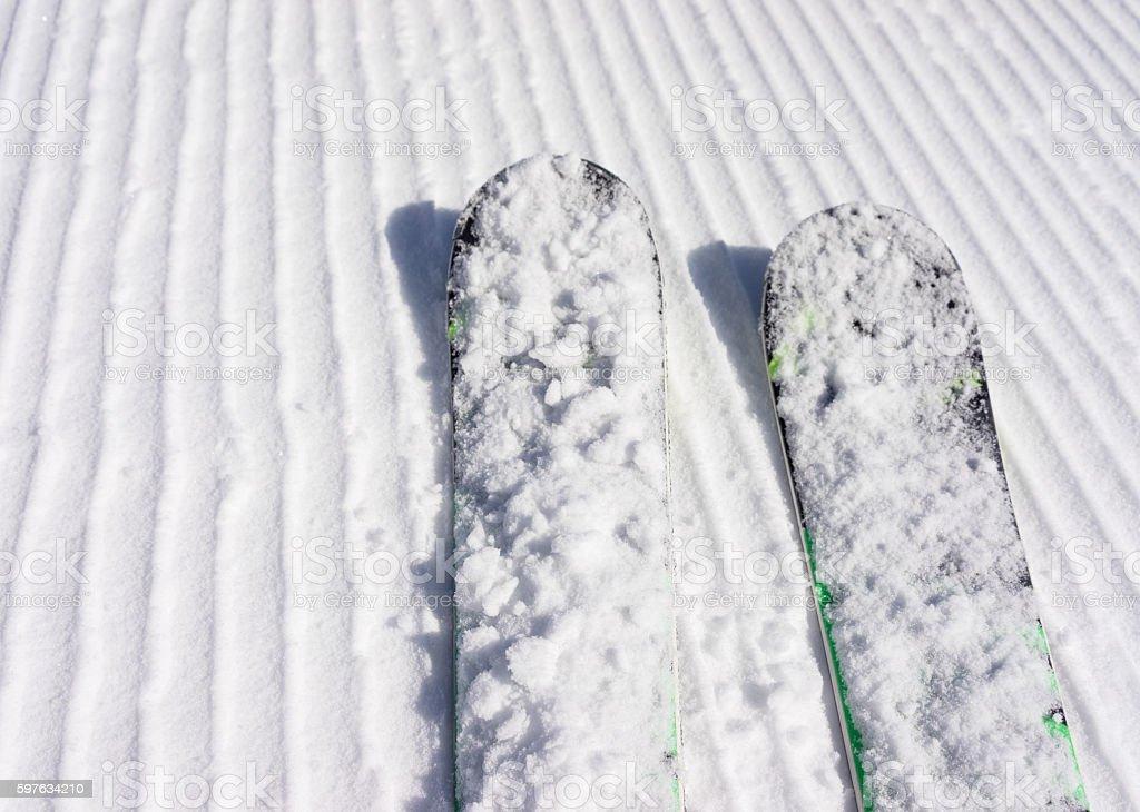 Pair of skis on a freshly groomed piste stock photo