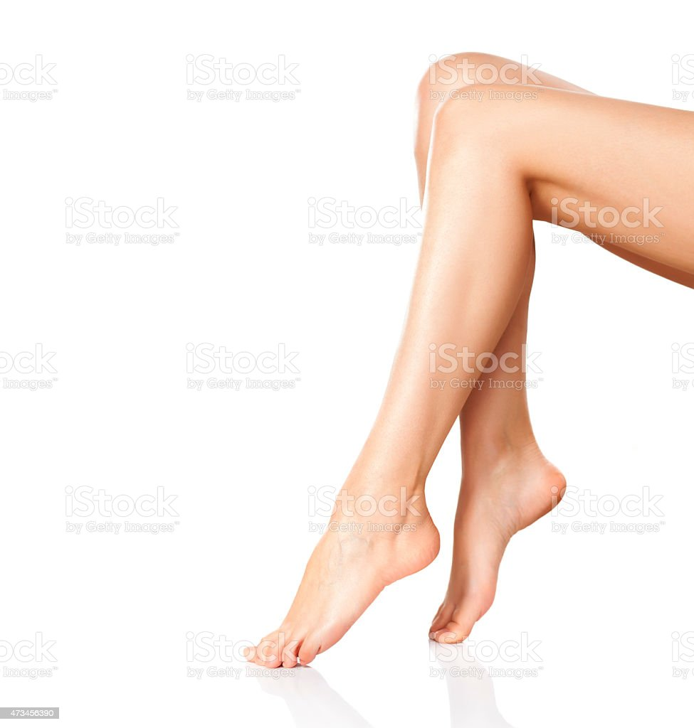 A pair of smooth female legs sitting with toes pointed stock photo