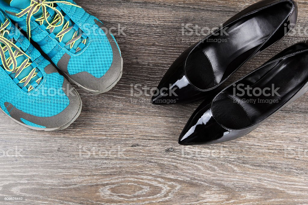 Pair of sneakers with classic black heeled shoes stock photo