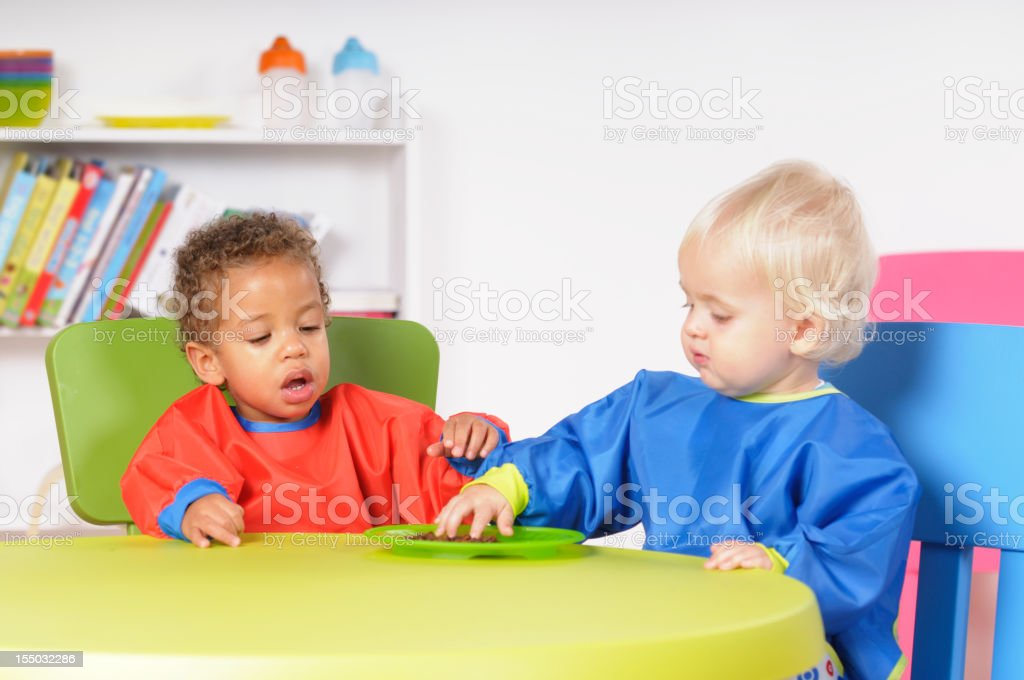 Pair Of Toddlers Sharing Raisins In A Nursery Setting stock photo