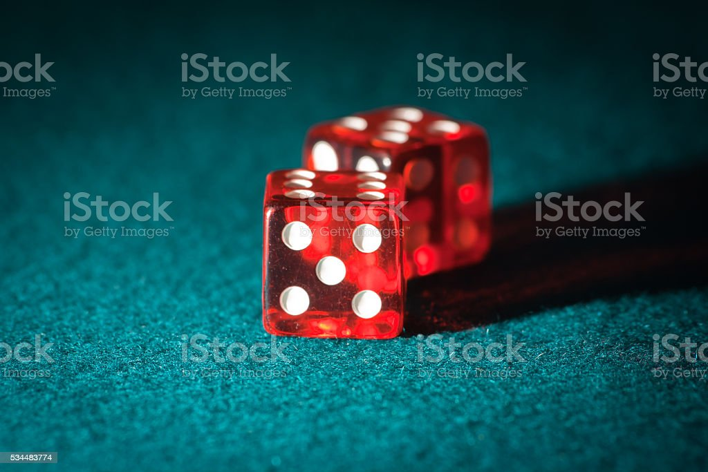 pair of transparent dice on a green table stock photo