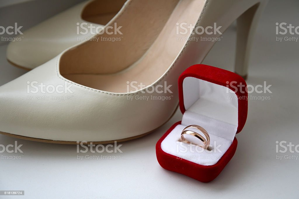 pair of wedding rings in a red box, cream shoes stock photo