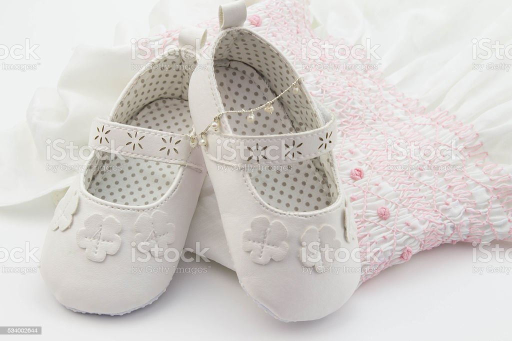 Pair of white baby shoes on embroidered white dress stock photo