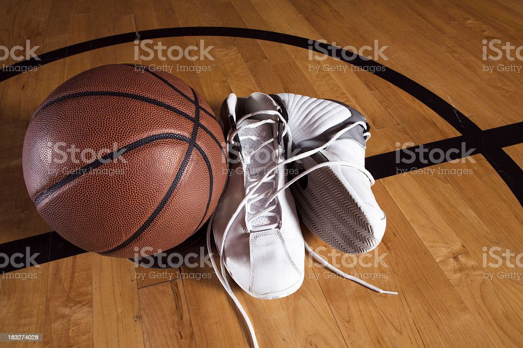 Pair of white basketball shoes next to basketball on court stock photo