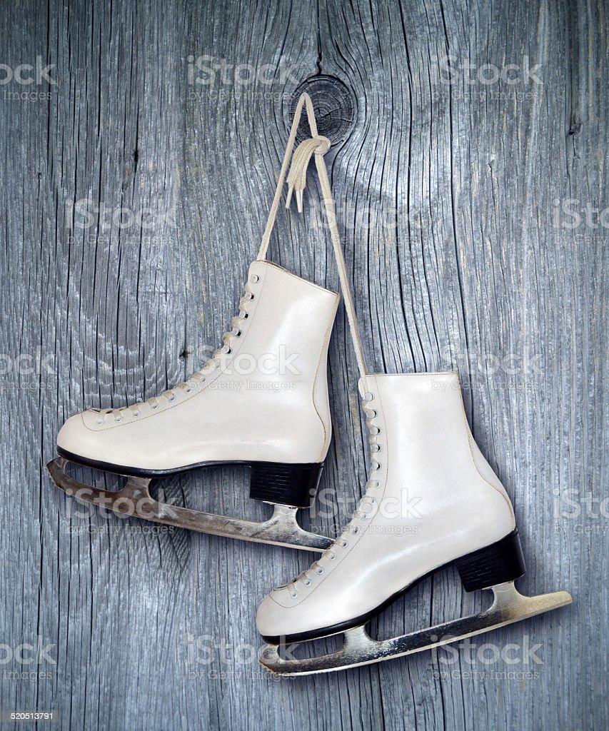 Pair of White Ice Skates on wooden  backround stock photo