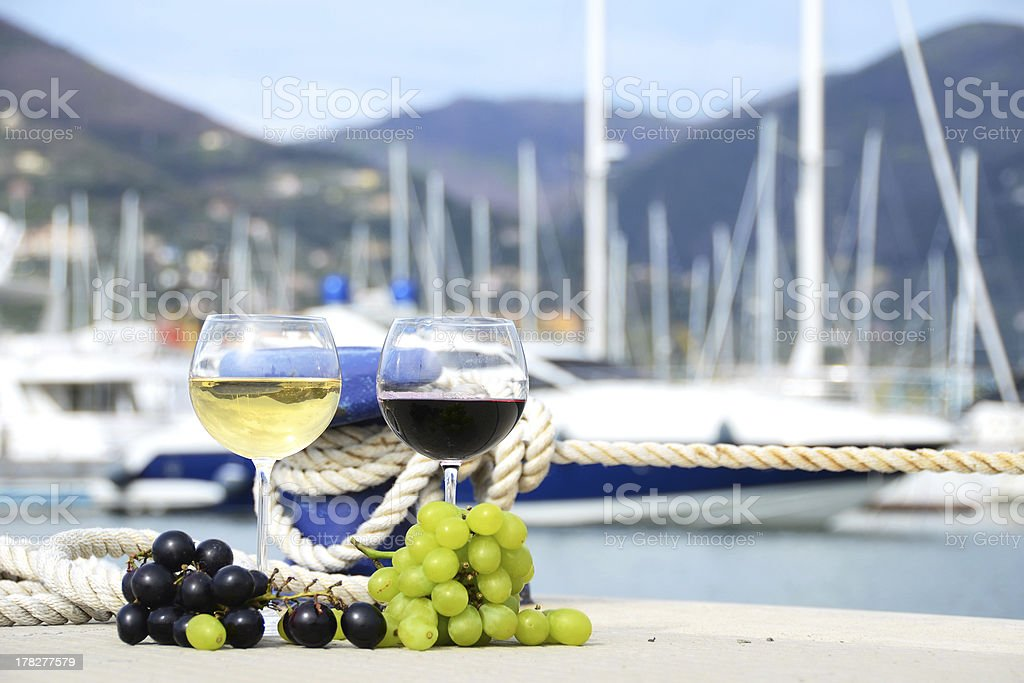 Pair of wineglasses and grapes against the yacht pier royalty-free stock photo