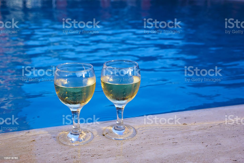 pair of wineglasses at the poolside stock photo