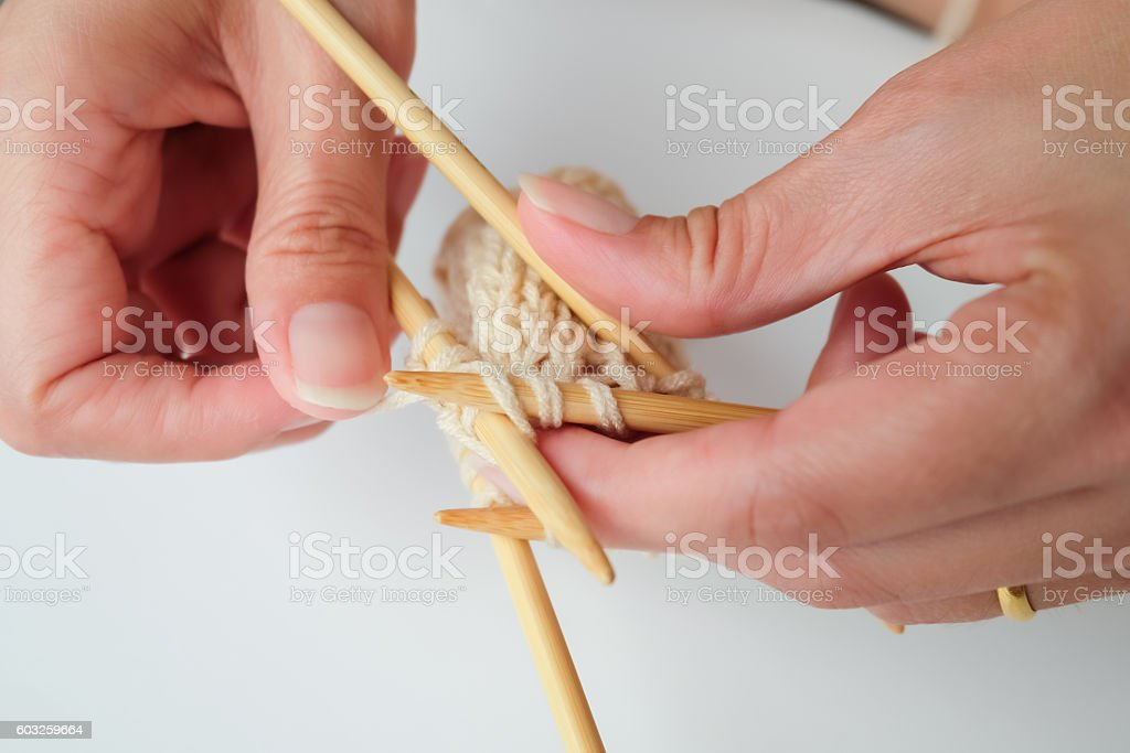 Pair of woman's hands and knitting needles isolated stock photo