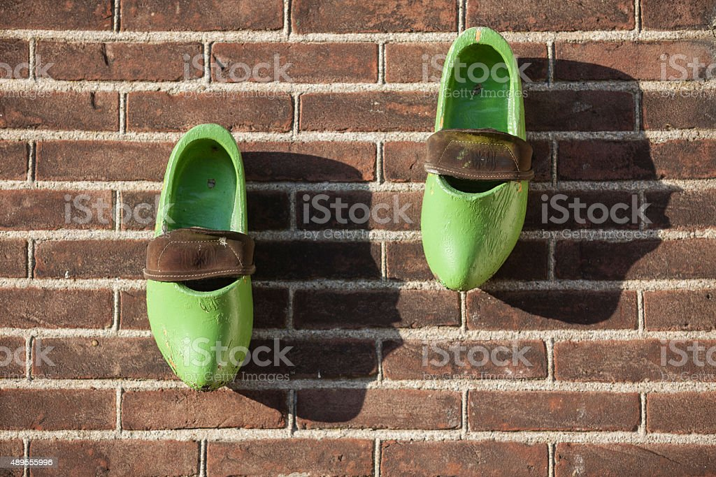 Pair Of Wooden Clogs on Brick Background In Amsterdam stock photo