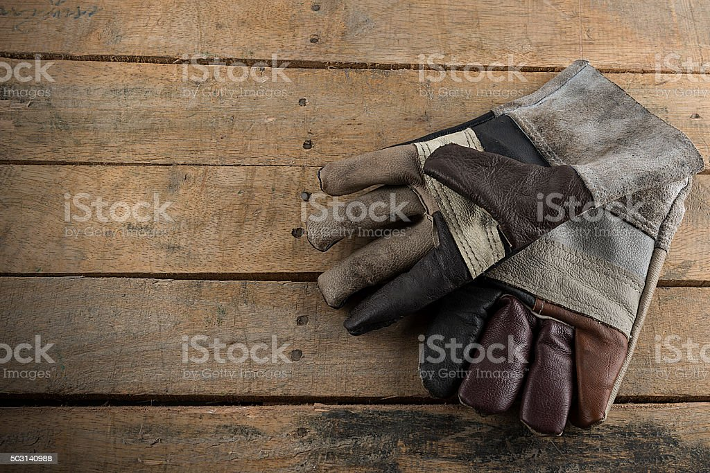 pair of work  leather glov lying on planks of wood stock photo