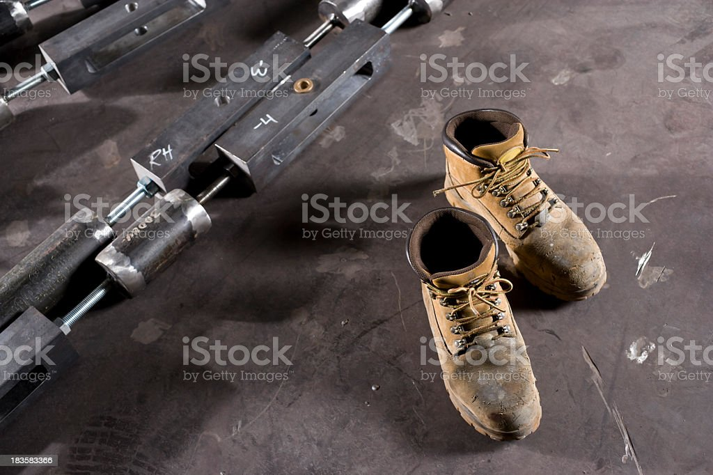 Pair of workers boots on factory floor stock photo