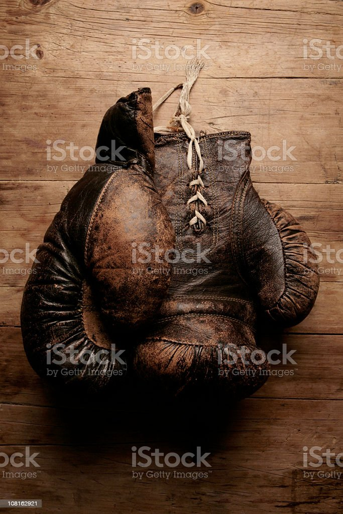 A pair of worn old boxing gloves on wooden table stock photo
