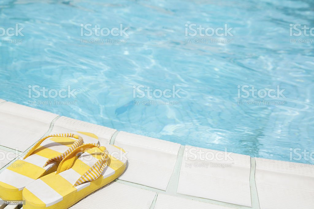 Pair of yellow flip flops by the pool side stock photo