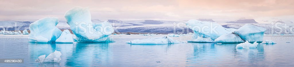 Pale blue icebergs floating in tranquil Arctic ocean lagoon Iceland stock photo