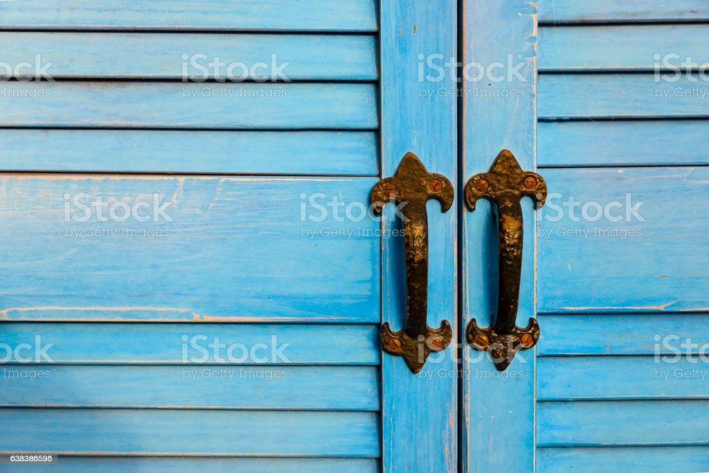 Pale blue painted slatted doors with two black iron handles stock photo