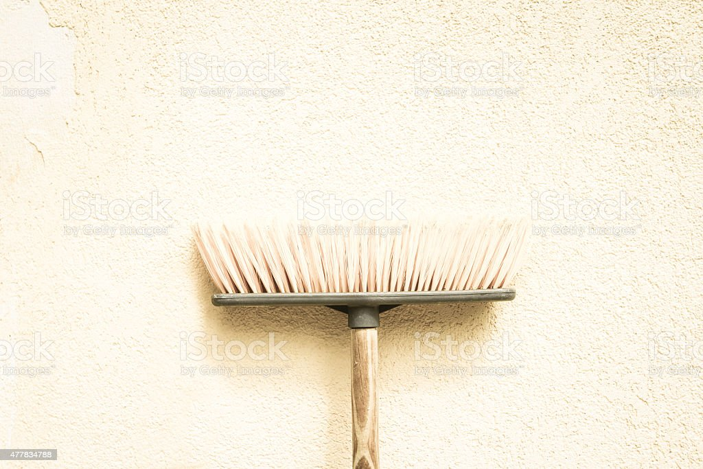Pale Cream-Colored Pushbroom On Rustic Matching Wall stock photo