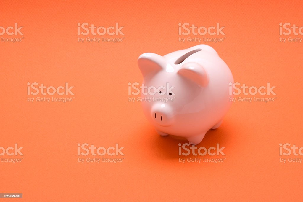 A pale pink piggy bank set on top of an orange table  royalty-free stock photo