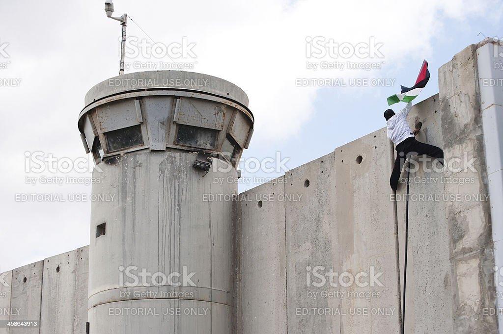 Palestinian climbs Israeli separation wall stock photo