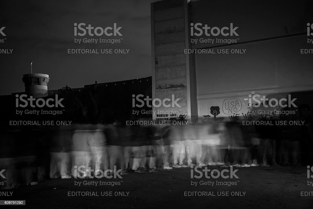 Palestinian laborers waiting in pre-dawn line at Bethlehem checkpoint stock photo