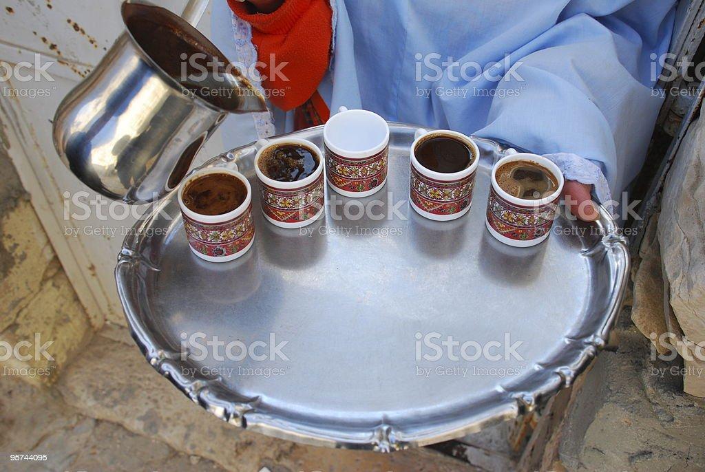 Palestinian woman pours coffee in Jerusalem royalty-free stock photo
