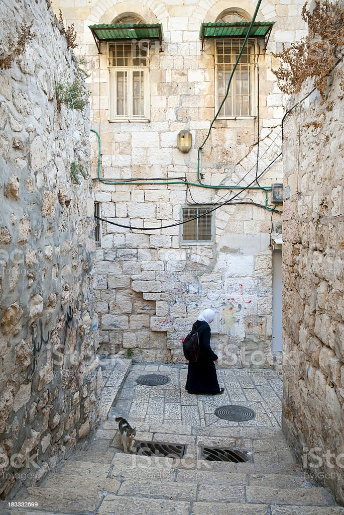 Palestinian woman walking in Muslim Quarter of Jerusalem's Old City royalty-free stock photo