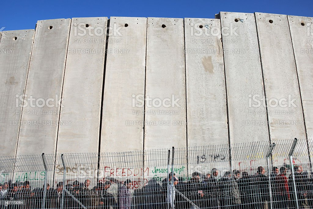 Line of people at tall wall in Palestine stock photo