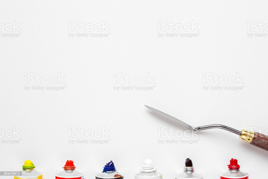 palette knife and oil paint tubes on white canvas stock photo