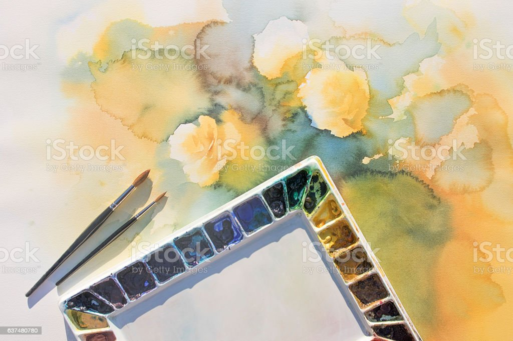 palette with brushes on watercolor background stock photo