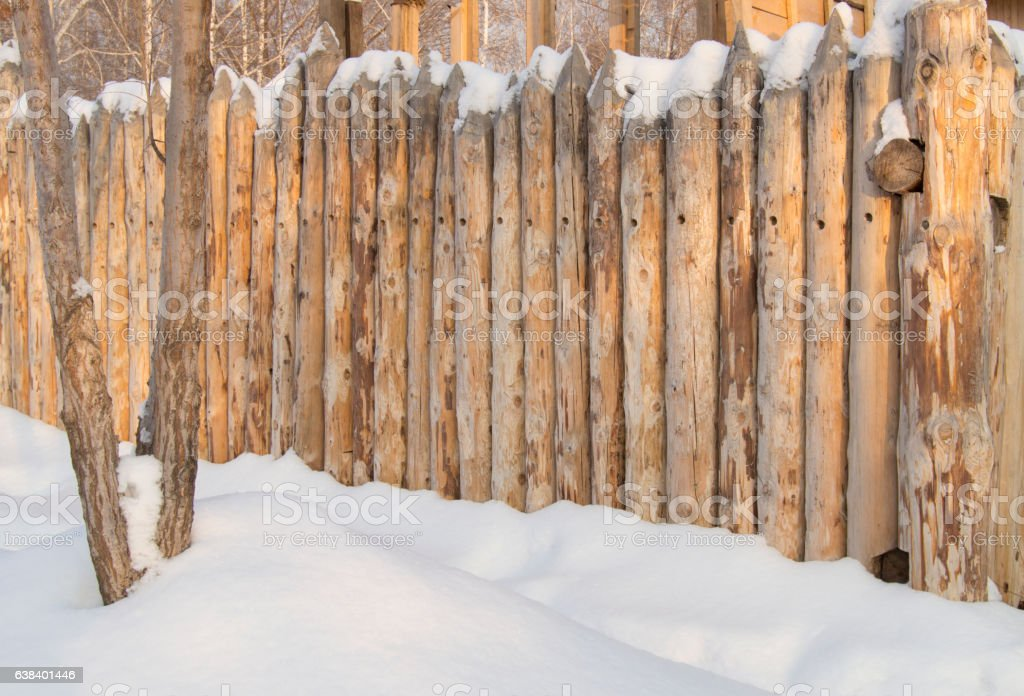 Paling, Wooden fence made of logs in the village, winter stock photo