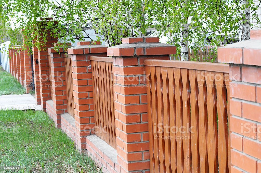 palisade fence with brick columns stock photo