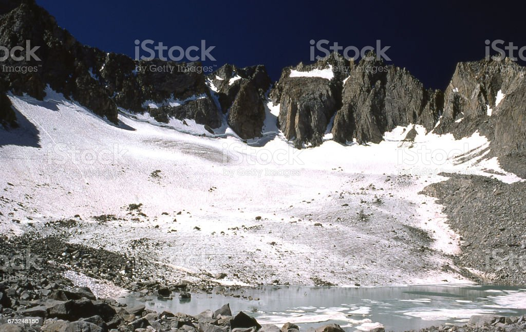 Palisade Glacier in the Sierra Nevada Mountains and glacial meltwater tarn at foot of glacier in summertime in the 1970s stock photo