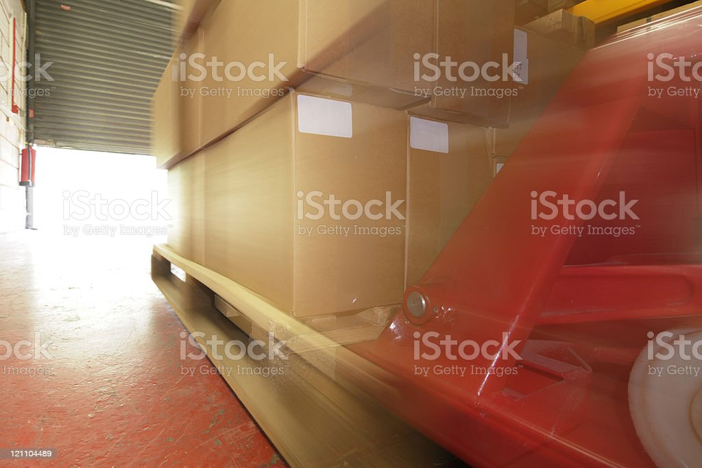 Pallet-truck Moving a Pallet Towards Open Roller Shutters royalty-free stock photo