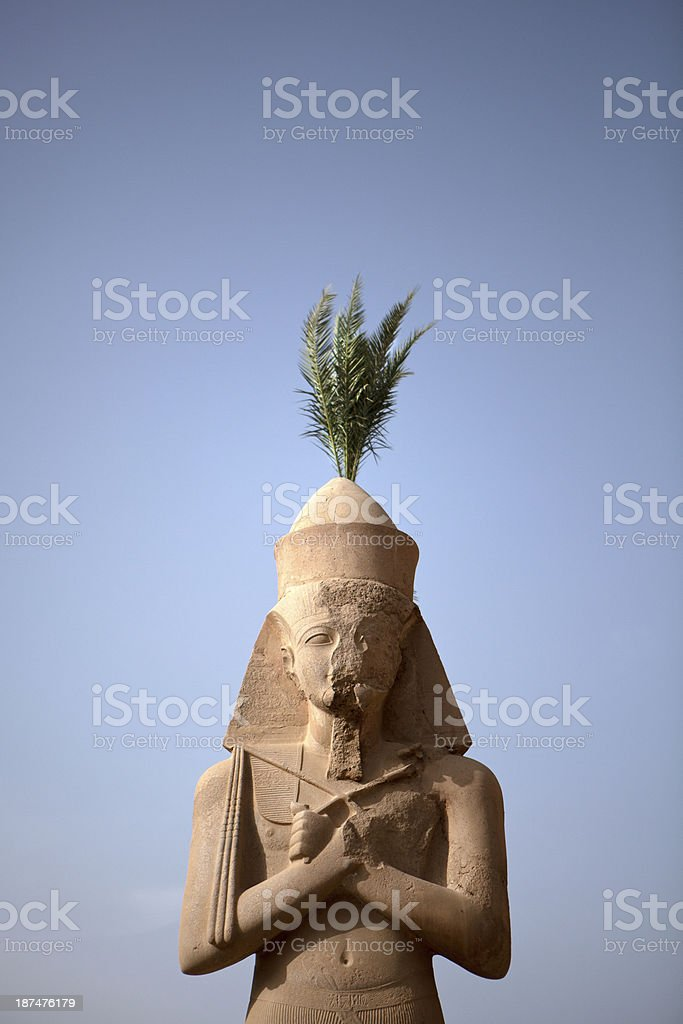 Palm coming out the top of Egyptian statue stock photo
