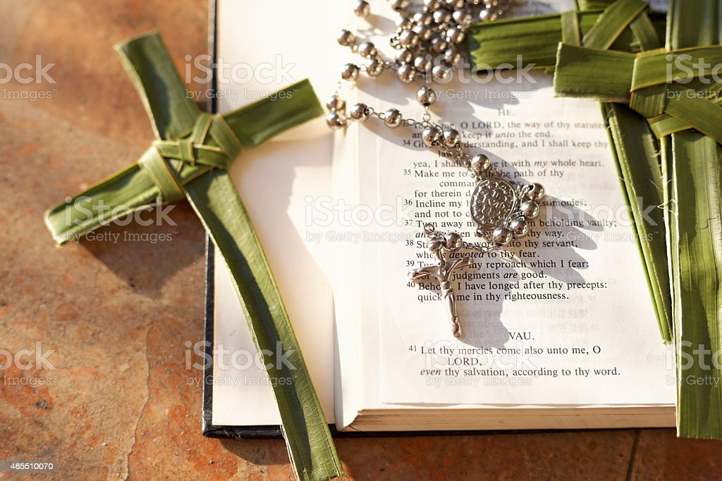 Palm cross, rosary beads sitting on an open Bible stock photo