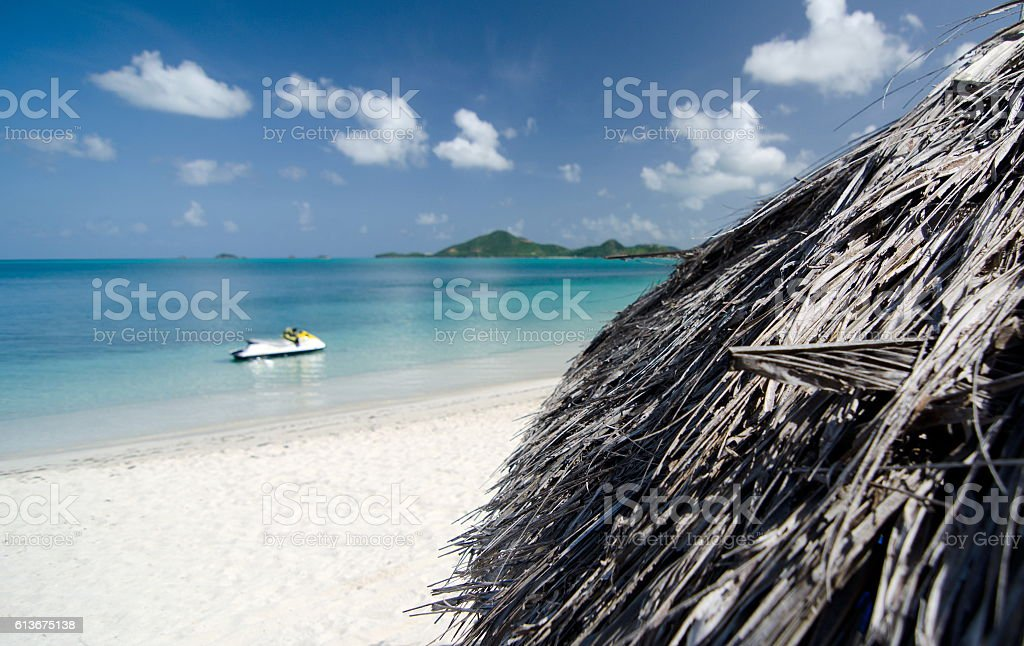Palm leaf umbrellas on beautiful Cocobay beach stock photo