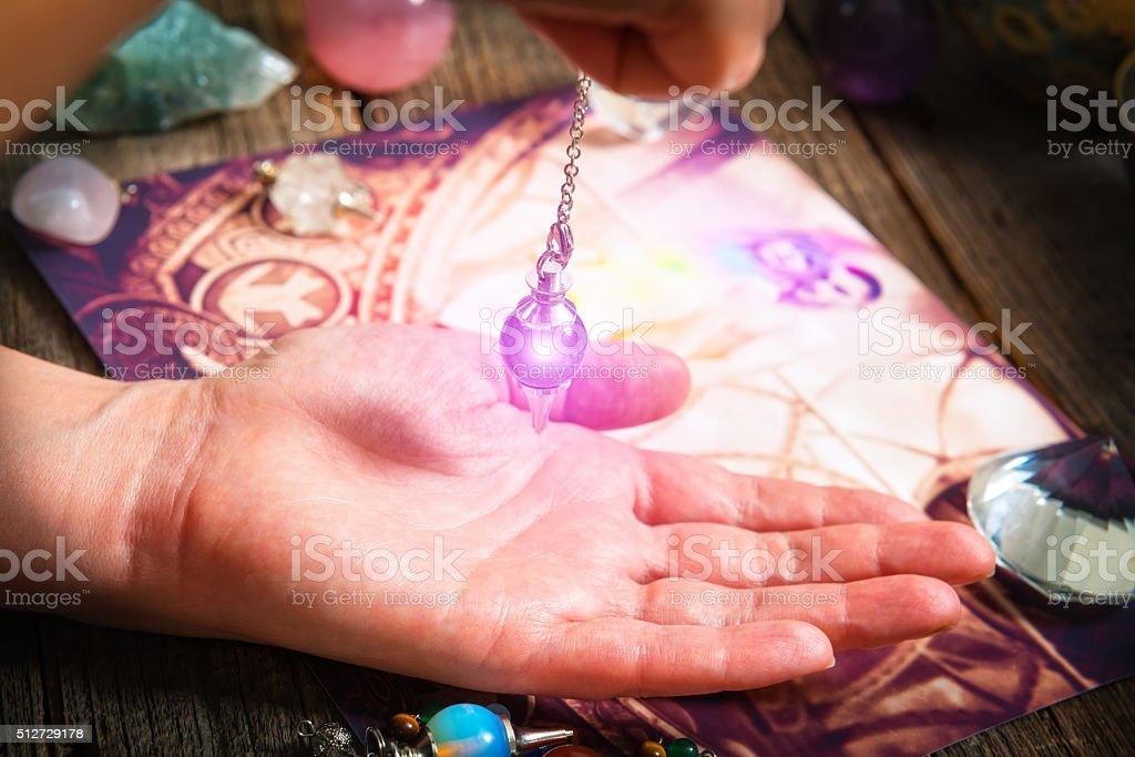 Palm reading with pendulum stock photo