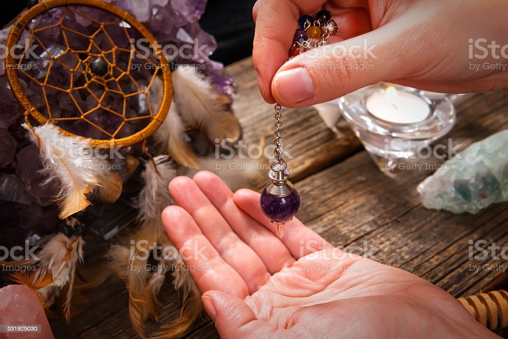 Palm reading with pendulum stock photo