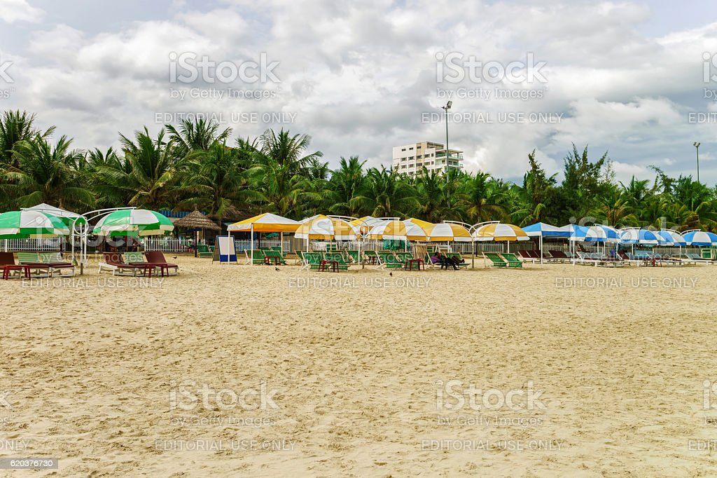 Palm shelters and people at China Beach in Danang stock photo