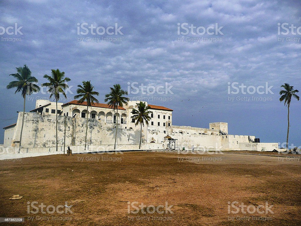 Palm trees casting shadows on Cape coast Castle stock photo