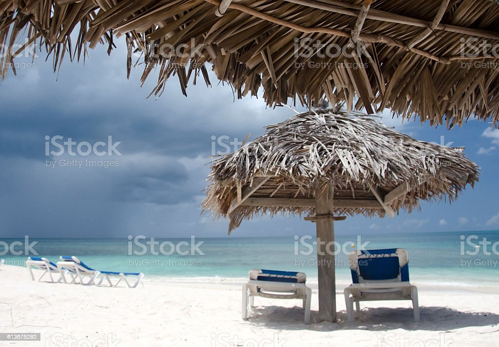 Palms, beach chairs and palm leaf umbrellas on beautiful Cocobay stock photo