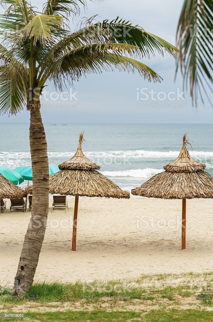 Palms shelter and sunbeds in China Beach in Da Nang stock photo